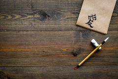 Chinese traditional calligraphy concept. Asian hieroglyph love in craft paper notebook near special writting pen on dark royalty free stock image