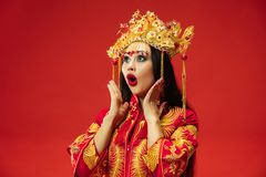 Chinese traditional woman. Beautiful young girl wearing in national costume. Chinese traditional graceful woman at studio over red background. Beautiful girl stock photography
