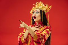 Chinese traditional woman. Beautiful young girl wearing in national costume. Chinese traditional graceful woman at studio over red background. Beautiful girl royalty free stock image