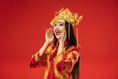 Chinese traditional woman. Beautiful young girl wearing in national costume. Chinese traditional graceful woman at studio over red background. Beautiful girl royalty free stock photo