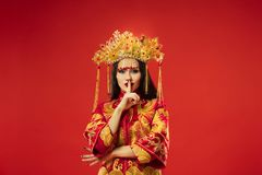 Chinese traditional woman. Beautiful young girl wearing in national costume. Chinese traditional graceful woman at studio over red background. Beautiful girl stock photos