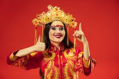 Chinese traditional woman. Beautiful young girl wearing in national costume. Chinese traditional graceful woman at studio over red background. Beautiful girl royalty free stock photography