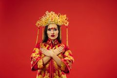 Chinese traditional woman. Beautiful young girl wearing in national costume. Chinese traditional graceful woman at studio over red background. Beautiful girl royalty free stock photos