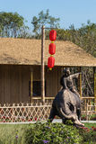 Chinese traditional houses before the boy riding on a cow sculpture Royalty Free Stock Image