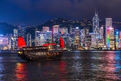 A Chinese traditional junk boa sailing passing famous Hong Kong skyline Stock Photo