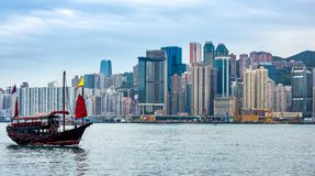 Chinese traditional junk boat in front of Hong Kong skyline. Chinese traditional junk boat in front of Hong Kong island city skyline with high skyscrapers stock images