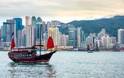 Chinese traditional junk boat in front of Hong Kong skyline. Chinese traditional junk boat in front of Hong Kong island city skyline with high skyscrapers royalty free stock photography