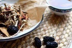 Chinese traditional medicine script. Herbal tea with jujubes, goji berries, gingseng roots and others on parchment paper on neutra royalty free stock images