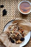 Chinese traditional medicine script. Herbal tea with jujubes, goji berries, gingseng roots and others on parchment paper on neutra royalty free stock photography