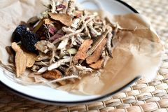 Chinese traditional medicine script. Herbal tea with jujubes, goji berries, gingseng roots and others on parchment paper on neutra stock photography