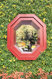 Window. Red octagonal window surrounded by chrysanthemum Royalty Free Stock Photography