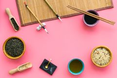 Chinese traditional symbols concept. Tea, rice, hieroglyph love, bamboo table mat, chopsticks, soy sause on pink. Background top view frame stock photography