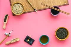 Chinese traditional symbols concept. Tea, rice, hieroglyph love, bamboo table mat, chopsticks, soy sause on pink. Background top view frame royalty free stock photo