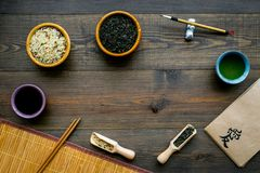 Chinese traditional symbols concept. Tea, rice, hieroglyph love, bambootabe mat, chopsticks, soy sause on dark wooden. Background top view frame stock images