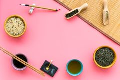Chinese traditional symbols concept. Tea, rice, hieroglyph love, bambootabe mat, chopsticks, soy sause on pink. Background top view frame royalty free stock photo