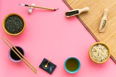 Chinese traditional symbols concept. Tea, rice, hieroglyph love, bambootabe mat, chopsticks, soy sause on pink royalty free stock photo