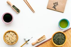 Chinese traditional symbols concept. Tea, rice, hieroglyph love, bambootabe mat, chopsticks, soy sause on white. Background top view stock photography