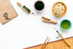 Chinese traditional symbols concept. Tea, rice, hieroglyph love, bambootabe mat, chopsticks, soy sause on white. Background top view royalty free stock images