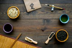 Chinese traditional symbols concept. Tea, rice, hieroglyph symbol, bambootabe mat, chopsticks, soy sause on dark wooden. Background top view frame royalty free stock image