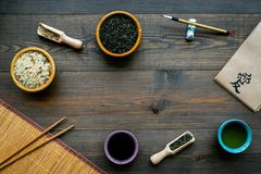 Chinese traditional symbols concept. Tea, rice, hieroglyph symbol, bambootabe mat, chopsticks, soy sause on dark wooden. Background top view frame royalty free stock photo