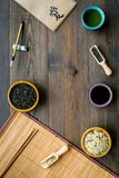 Chinese traditional symbols concept. Tea, rice, hieroglyph symbol, bambootabe mat, chopsticks, soy sause on dark wooden. Background top view frame stock image