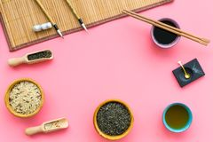 Chinese traditional symbols concept. Tea, rice, hieroglyph symbol, bambootabe mat, chopsticks, soy sause on pink. Background top view frame royalty free stock photo