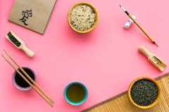 Chinese traditional symbols concept. Tea, rice, hieroglyph symbol, bambootabe mat, chopsticks, soy sause on pink. Background top view frame royalty free stock photography