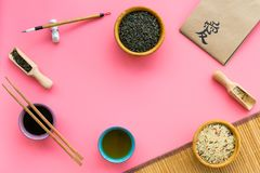 Chinese traditional symbols concept. Tea, rice, hieroglyph symbol, bambootabe mat, chopsticks, soy sause on pink. Background top view frame stock images