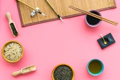 Chinese traditional symbols concept. Tea, rice, hieroglyph symbol, bambootabe mat, chopsticks, soy sause on pink. Background top view frame stock photography