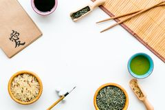 Chinese traditional symbols concept. Tea, rice, hieroglyph symbol, bambootabe mat, chopsticks, soy sause on white. Background top view stock photos