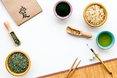 Chinese traditional symbols concept. Tea, rice, hieroglyph symbol, bambootabe mat, chopsticks, soy sause on white. Background top view royalty free stock photos