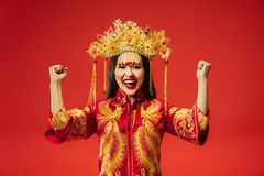 Chinese traditional woman. Beautiful young girl wearing in national costume. Chinese traditional graceful woman at studio over red background. Beautiful girl royalty free stock images