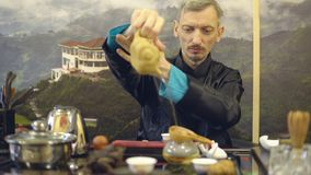 Chinese traditions. Master man brews tea at the ceremony.  stock video