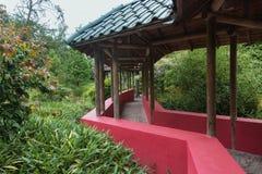 Chinese tuin die door een behandelde gangtribune met wordt gekruist Stock Afbeeldingen