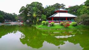 Chinese tuin met paviljoen en groene vijver stock footage