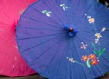 Chinese umbrellas with colorful designs. Closeup of two Chinese umbrellas with colorful designs in blue and pink stock photo