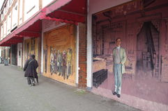 Old man walking past Chinatown murals Stock Images