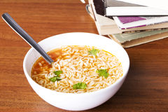 Chinese, vegetable, pasta soup next to books. Royalty Free Stock Image