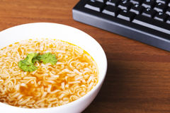 Chinese, vegetable, pasta soup next to keyboard. Stock Images
