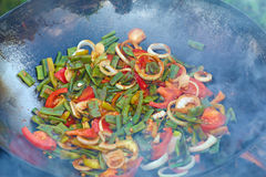 Chinese vegetables in wok over an open fire. Stock Photo