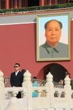 Chinese veiligheidsagent op de achtergrond van een portret van Mao Zedong Stock Afbeelding