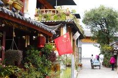 Chinese vlag die van een huis in een straat van Lijiang in Yunnan, China uitpuilen stock afbeelding