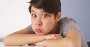 Chinese vrouw die dwaze gezichten maken bij camera stock afbeelding