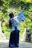 Chinese vrouw in traditionele Blauwe en witte Hanfu-kleding die zich in het midden van mooie poort bevinden stock fotografie
