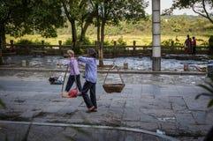 Chinese vrouw twee die landbouwproducten op schouderpolen dragen in een straat van de stad van Yangshuo in China Royalty-vrije Stock Foto's