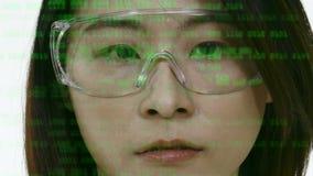 Chinese vrouwelijke wetenschapper die in veiligheidsbril code bekijken stock footage