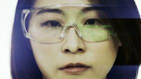 Chinese vrouwelijke wetenschapper die in veiligheidsbril code bekijken stock video