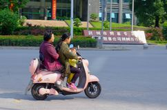 Chinese vrouwen en kind berijdende autoped in China Royalty-vrije Stock Foto