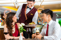 Chinese waiter serving dinner in elegant restaurant or Hotel. Asian Chinese couple - Man and women - or lovers having a date or romantic dinner in a fancy royalty free stock photography