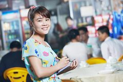 Chinese waitress of restaurant with menu. Young Chinese waitress girl of street restaurant in china with menu waiting an order Stock Photography